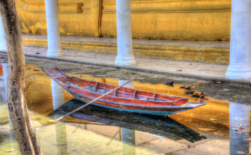 Colorful rowboat in shallow water after a flood at a Buddhist Temple in Thailand. ASIA Boat Brddhist Calm Colorful Day Nature No People Oar Old Outdoors Peaceful Picturesque Quite Reflections In The Water Relaxing Religon Rowboat. Rowing Serene Shallow Water Temple Thialand Tranquil Water