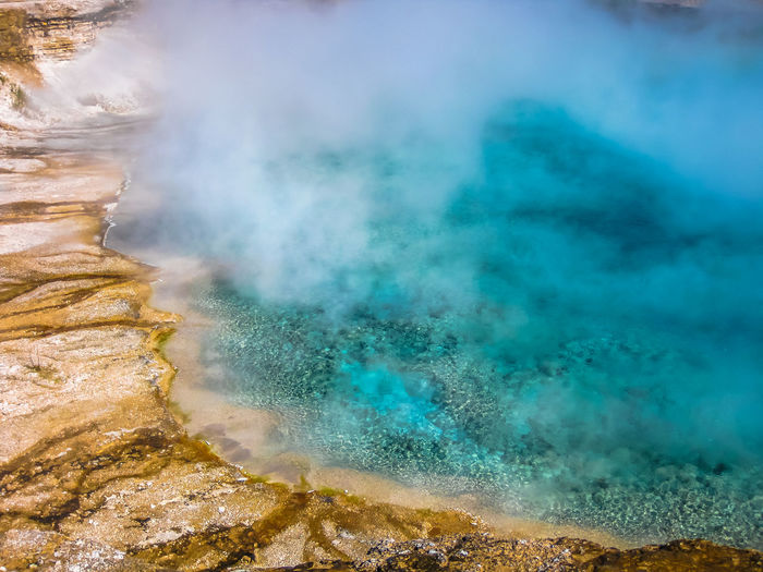 Closeup of Morning Glory Pool, a hot spring in the Upper Geyser Basin in Yellowstone National Park, Wyoming and Montana, United States. Castle Geyser erupts with hot water and steam with pools of thermophilic bacteria and is a cone geyser in the Upper Geyser Basin of Yellowstone National Park, Wyoming, United States. Dramatic view of dead trees and travertine terraces rock formations made of crystallized calcium carbonate in Mammoth Hot Springs, Yellowstone National Park in Wyoming and Montana, United States. Gaiser Grand Prismatic Lake Wyoming Landscape Yellowstone Yellowstone National Park Yellowstone National Park. Beauty In Nature Day Erupting Geology Geyser Grand Prismatic Grand Prismatic Spring Heat - Temperature Hot Spring Lake Motion Mountain Nature No People Outdoors Park Physical Geography Pool Power In Nature Scenics Sky Smoke - Physical Structure Steam Vulcano Water