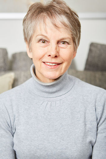 Close-Up Portrait Of Senior Woman Sitting At Home