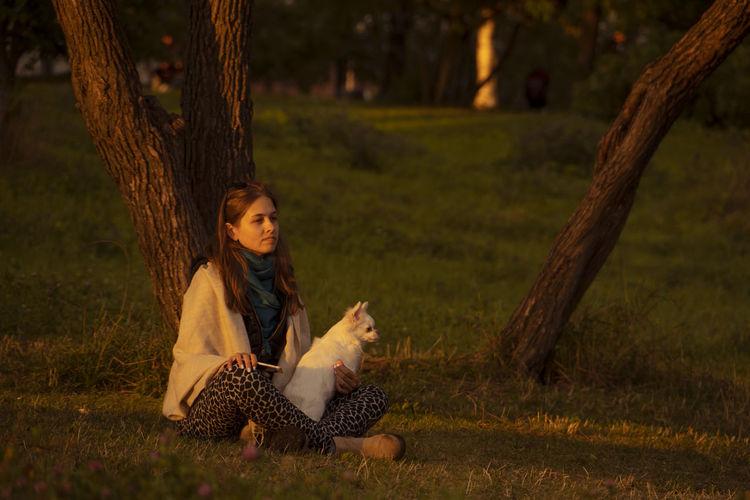 Portrait of woman sitting on tree trunk
