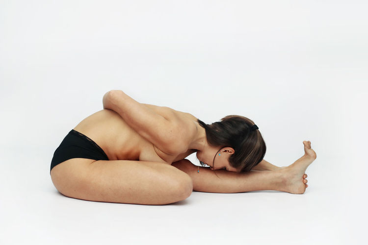 Midsection of woman lying on white background