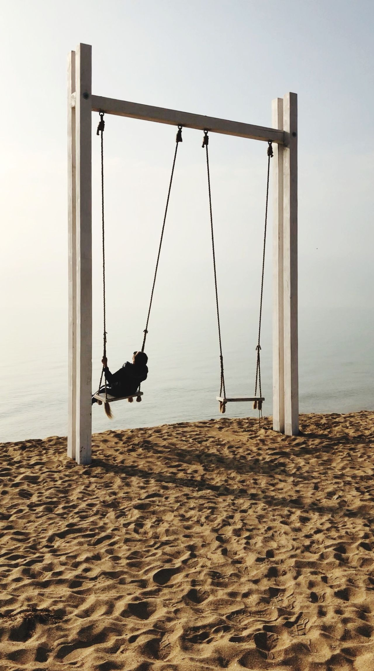 Rear view of mature woman swinging at sandy beach