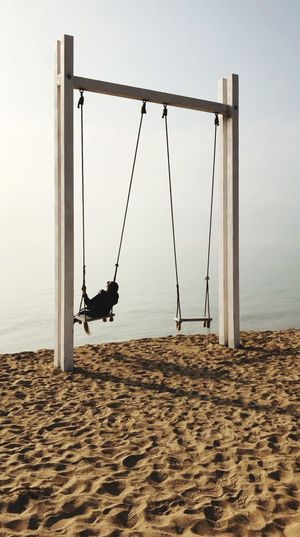 Low angle view of swing at beach against sky