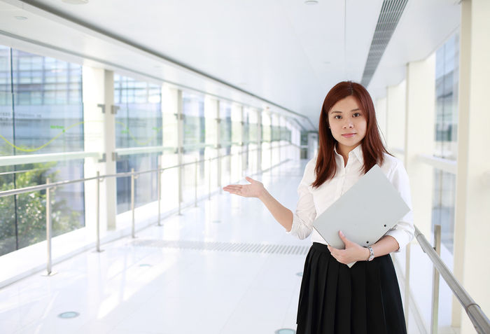Business File Adult Businesswoman Career Day Holding Indoors  Job Looking At Camera Occuaption One Person Open Real People Smile Standing Welcome Welcome To My World Well-dressed Young Adult Young Women