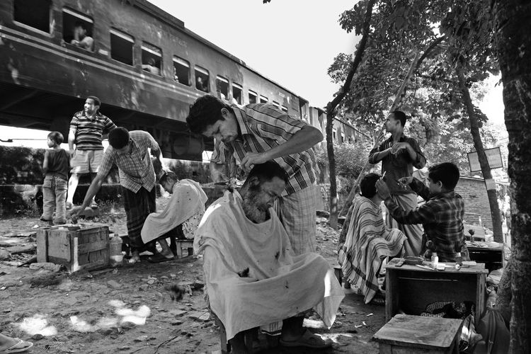 Lower income people preparing themselves and getting hair cut in an open place under a banyan tree for coming Eid-ul-Adha in couple of days. Eid Mubarak Large Group Of People Men Side View Full Length Street Standing Small Business Outdoors Street Market Train Travel Eiduladha Nikon Dhaka, Bangladesh EyeEm Bangladesh EyeEm Best Shots The Street Photographer - 2017 EyeEm Awards