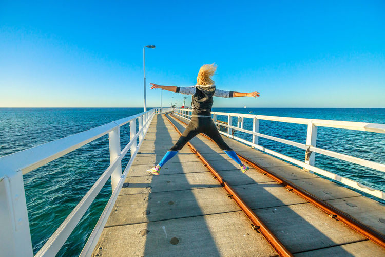 Western Australia travel freedom concept. Happy caucasian woman jumping at Busselton jetty in Busselton, Western Australia. Female jumper over iconic wooden pier in WA, Australia. Steam Train Train Australia Jetty Busselton Busselton Jetty Busselton Western Australia Busseltonjetty Western Australia Beach Station Travel Pier Tourist Railway Railway Track Sea Transportation Tourist Attraction  Landmark Sunset Woman Girl Sunlight Water One Person Horizon Over Water Sky Horizon Railing Beauty In Nature Lifestyles Leisure Activity Full Length Scenics - Nature Rear View Nature Real People Day Women Blue Hair Human Arm Outdoors Looking At View