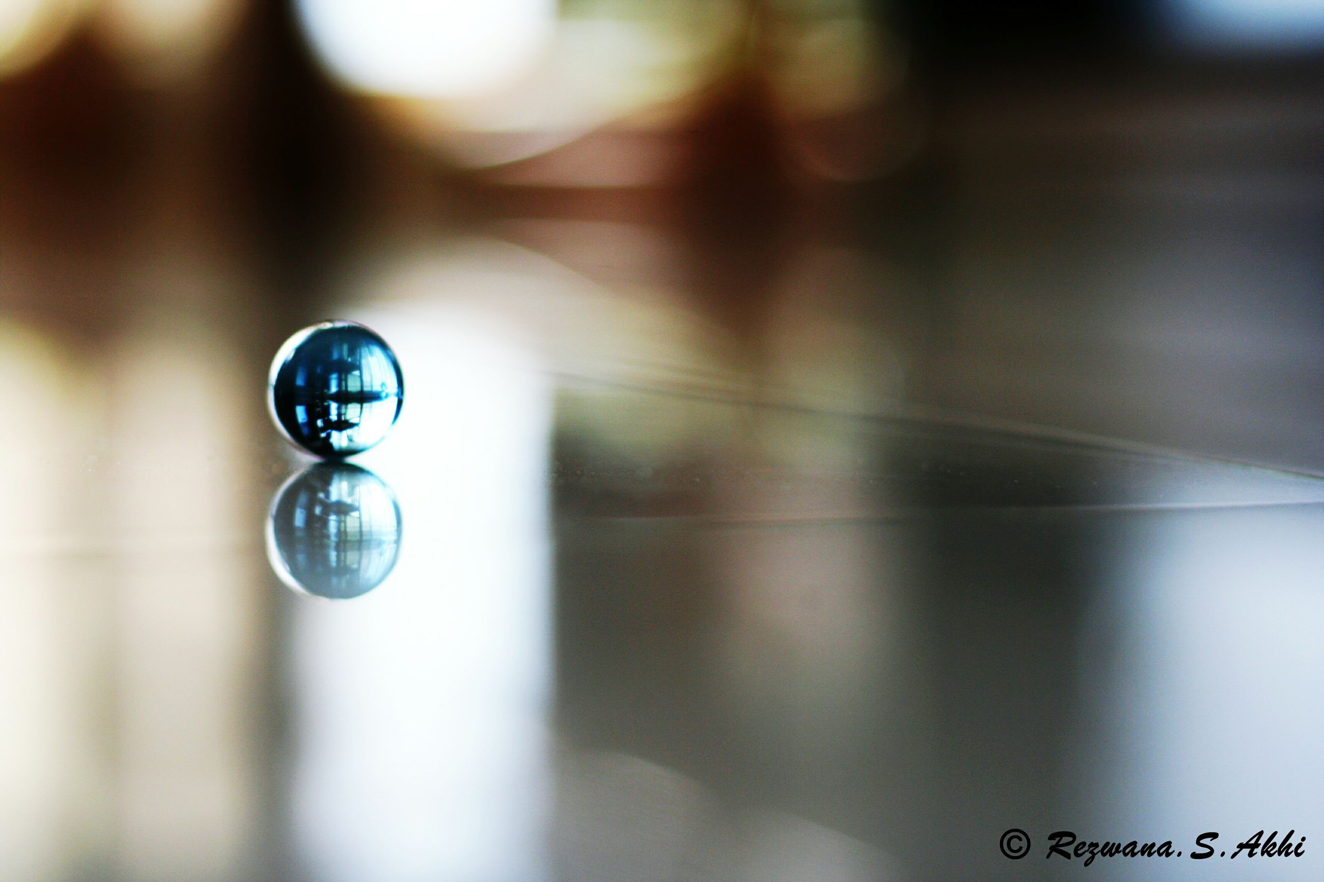 lighting equipment, focus on foreground, indoors, close-up, selective focus, hanging, low angle view, illuminated, electricity, reflection, no people, ceiling, glass - material, light bulb, electric light, day, decoration, technology, transparent, sphere