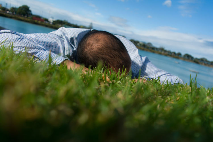 Surface level view of man lying on grassy field