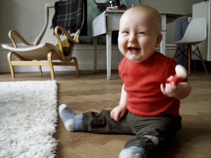 Happy Baby Boy Sitting On Floor At Home