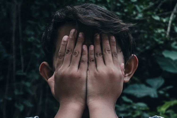 Close-up portrait of a boy covering face