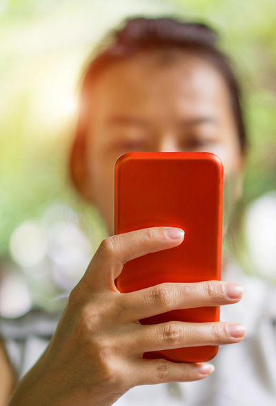 Young asian woman touching red smartphone 4g 5G Asian  Hand Holding Holding Hands Red Communication Female Focus On Foreground Handholding Hold Holding Human Hand IPhone Internet Mobile Phone One Person Portable Information Device Real People Smart Phone Technology Touching Using Phone Wireless Technology Women