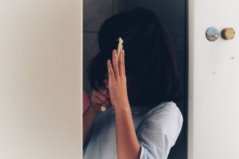 Close-up of girl combing hair at home