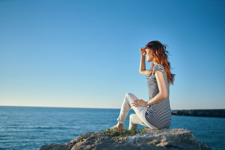 Woman sitting by sea against clear sky