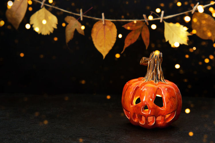Close-up of illuminated pumpkin against orange wall during halloween