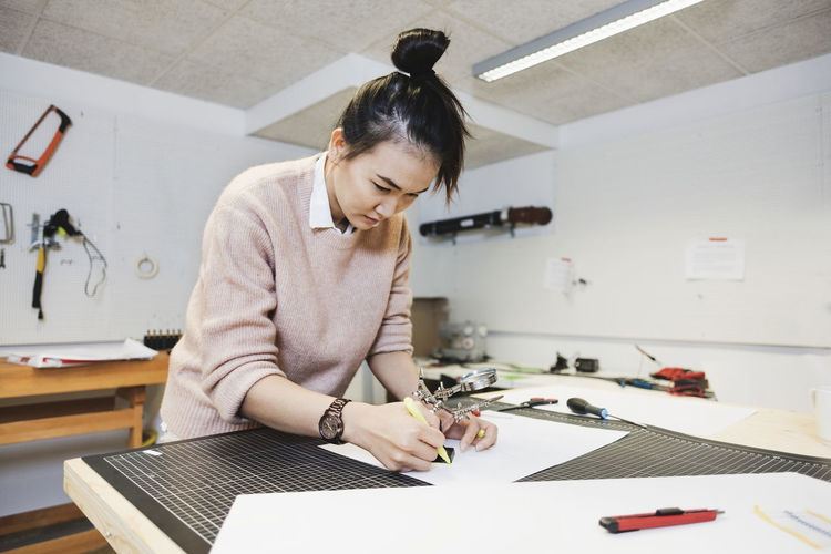 Businesswoman planning on paper at table in creative office