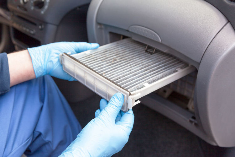Replacing an old car cabin air filter Hand Protective Workwear Protective Glove Repairing Technician Car Working Replace Air Filter Pollen Filter Car Interior Car Air Filter Air Conditioner Auto Mechanic Maintenance Automotive Industry Dust Dirt Dirty Allergen Pollution Ventilation Change