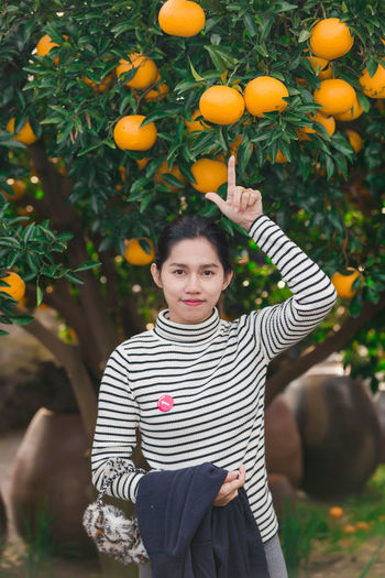 Portrait of woman standing pointing at oranges growing on tree