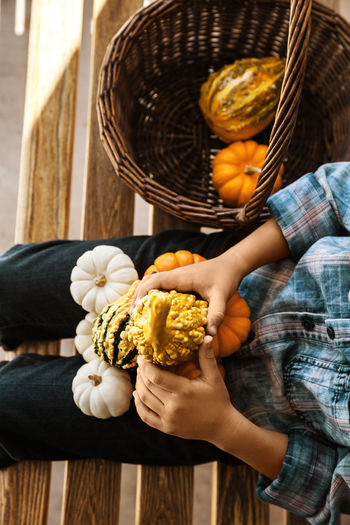 Midsection Of Person Holding Pumpkins