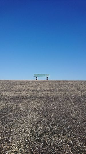 Bench on landscape against clear sky