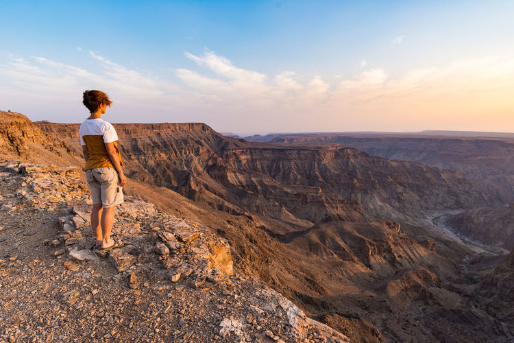 One person looking at the Fish River Canyon, scenic travel destination in Southern Namibia. Expansive view at sunset. Wanderlust traveling people. Keywords: fish river canyon,one person,looking at view,river,canyon,real people,expansive,people traveling,summer,namibia,travel destinations,valley,Landscape,cliff,sightseeing,vacation,desert,top,adventure,female,travel,mountains,exploration,summit,scenic,tourism,outdoors,panorama,landmark,majestic,above,famous,scenics,panoramic,wide-angle,clear sky,sunlight,viewpoint,idyllic,national park,horizon,remote,tourist,highland,relaxation,africa,happiness,extreme terrain Beauty In Nature Casual Clothing Environment Full Length Leisure Activity Lifestyles Mountain Mountain Range Nature Non-urban Scene One Person Outdoors Real People Rock Rock - Object Rock Formation Scenics - Nature Sky Solid Standing Tranquil Scene Tranquility