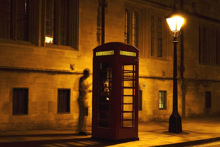 Full length of man at telephone booth