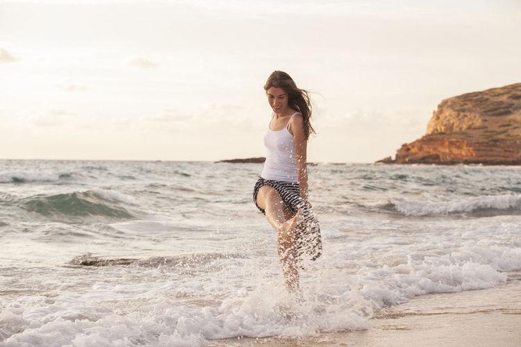 Full length of woman enjoying at beach