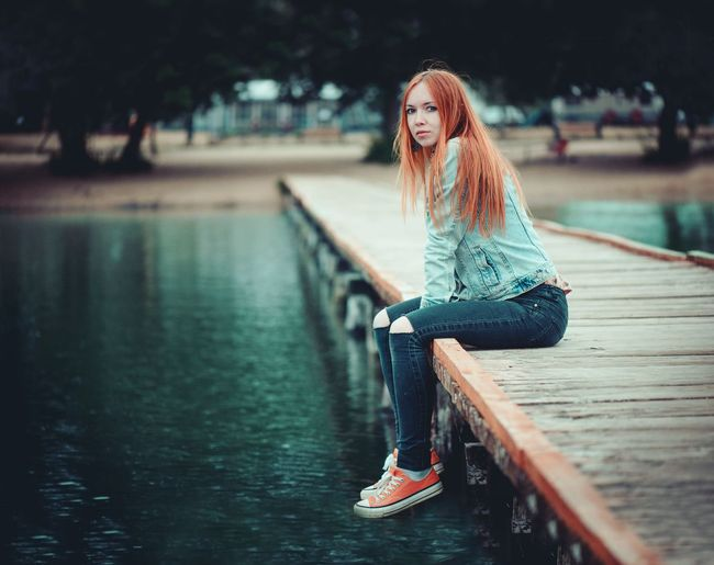 Portrait of woman sitting on pier over lake