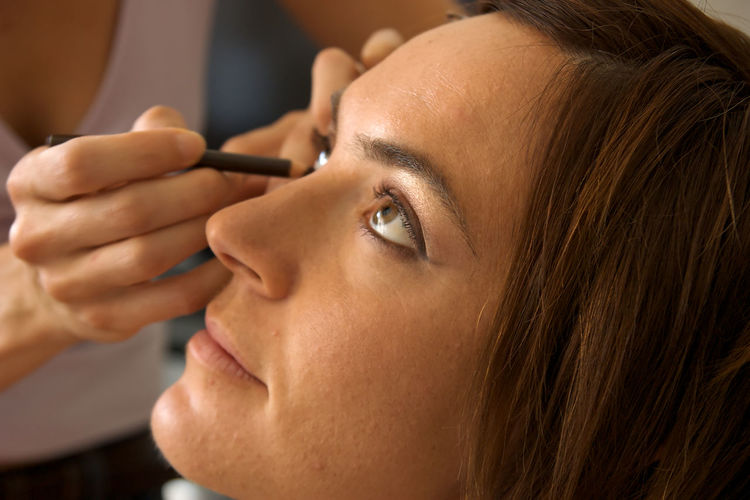 Midsection Of Beautician Applying Eyeliner On Woman Eye