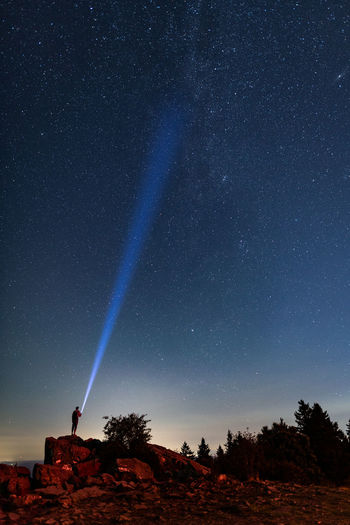 Person holding flashlight while standing on rock formation against star field