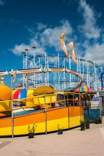 Carnival Rollercoaster Architecture Beach Blue Built Structure Cloud - Sky Container Day Industry Land Mode Of Transportation Nature Nautical Vessel No People Outdoors Pier Sky Sunlight Transportation Water Yellow