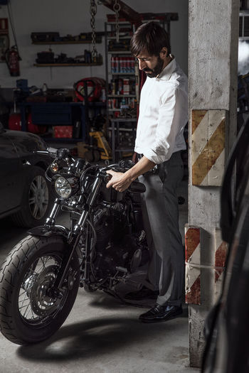 My best motorbike One Person Mode Of Transportation Standing Land Vehicle Transportation Adult Motor Vehicle Mechanic Garage Side View Occupation Motorbike Proud Biker Gentlemen Afterwards Dubious Motorcicle Engine Auto Repair Shop Bike Shop Portrait Real People Indoors  White Shirt
