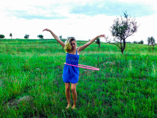 Having fun EyeEmNewHere Fashion Adult Arms Raised Beautiful Woman Blue Day Field Front View Full Length Fun Grass Green Color Happiness Hullahoop Human Arm Leisure Activity Nature One Person Outdoors People Sky Standing Young Adult Young Women