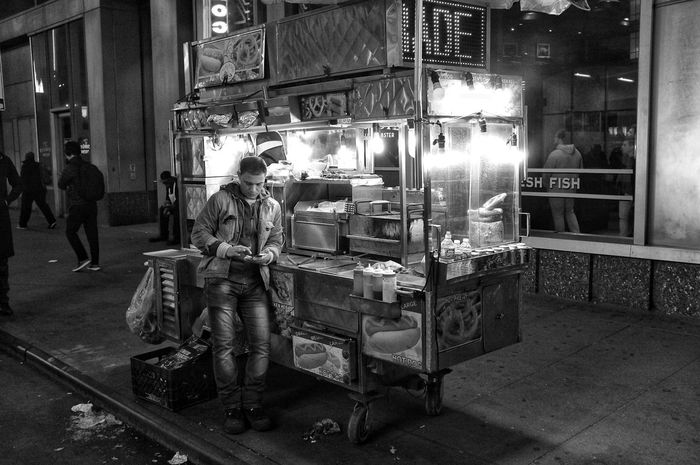 Texting Vendor Times Square NYC NYC Street Photography Illuminated Building Exterior Built Structure Night Architecture City Incidental People Street Real People Outdoors