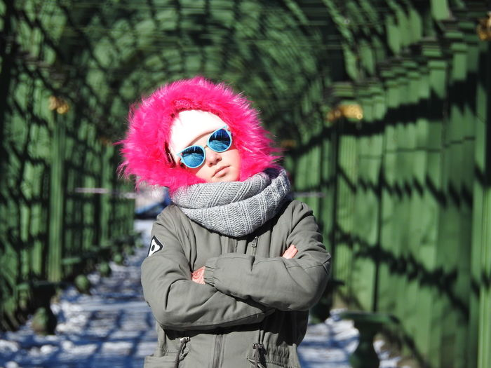 Portrait of girl in warm clothing with arms crossed standing at park