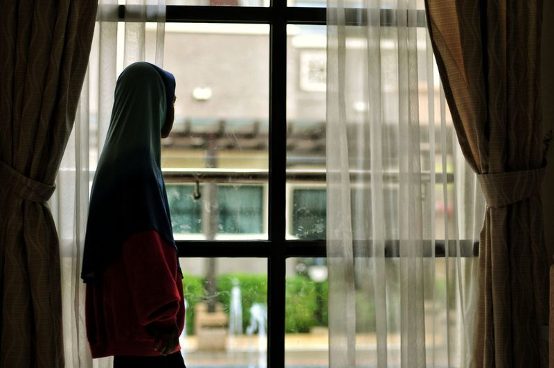 Side View Of Boy Wearing Hooded Shirt Looking Through Window At Home