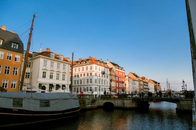 Canal amidst buildings against clear sky