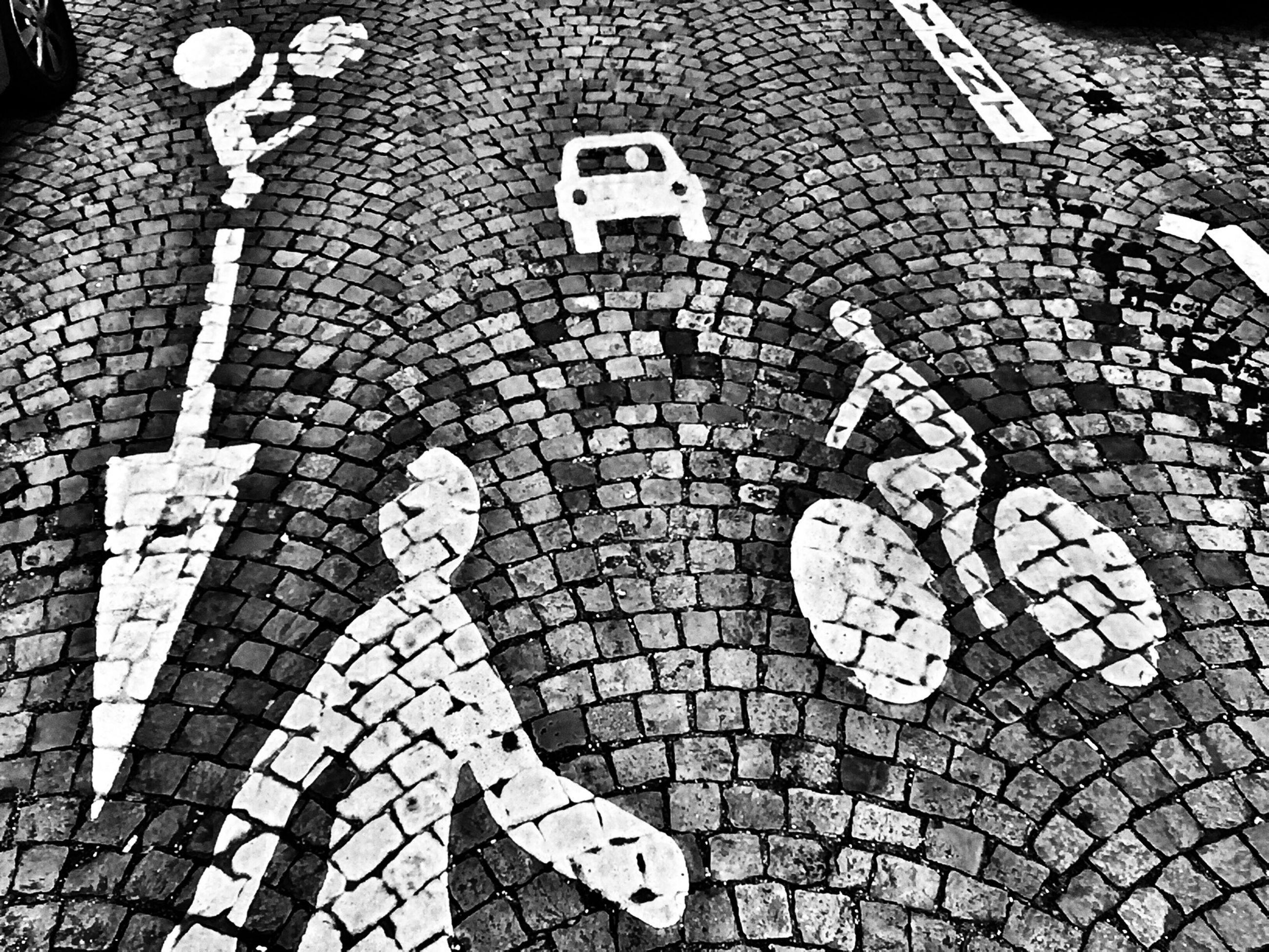 high angle view, cobblestone, paving stone, street, communication, text, pattern, sidewalk, footpath, road marking, western script, tiled floor, pavement, shadow, day, outdoors, sunlight, tile, capital letter, asphalt