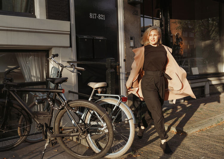 Portrait of woman with bicycle in city