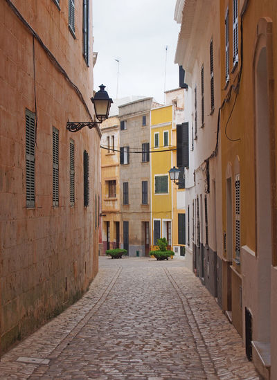 a typical town street in ciutadella menorca with winding curved cobbled road old traditional painted houses and street lamps Architecture Building Exterior Built Structure Building City Direction The Way Forward Residential District Street Footpath Town Cobblestone Narrow Alley Window No People Outdoors Road Nature Transportation Long Row House