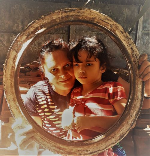Portrait of smiling mother with cute daughter seen through circular equipment