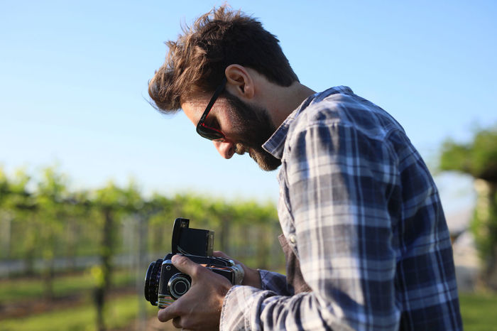 Camera - Photographic Equipment Casual Clothing Concentration Day Digital Single-lens Reflex Camera Eyeglasses  Field Leisure Activity Nature One Person Outdoors People Photographing Photography Themes Real People Side View Sky Technology Tree Young Adult