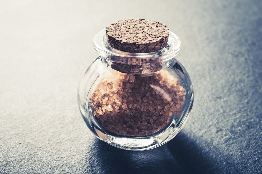 Close-Up Of A Brown Raw Sugar In A Small Glass Bottle Closed With A Cork Stopper On Slate Stone Cooking Diet Ingredients Macro Photography Raw Sugar Bottle Brown Close-up Closed Concept Container Cork - Stopper Flavoring Food And Drink Glass High Angle View Kitchen Less Raw Sugar Slate Sweet Sweetener Table Unhealthy Eating