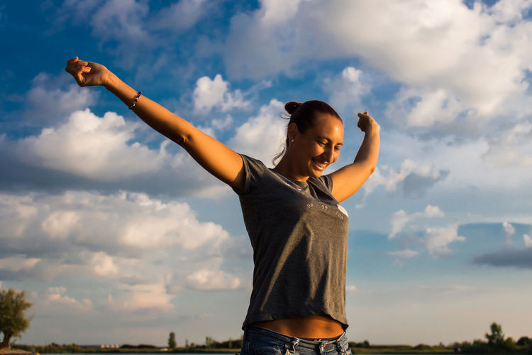 Smiling woman with arms outstretched standing against sky
