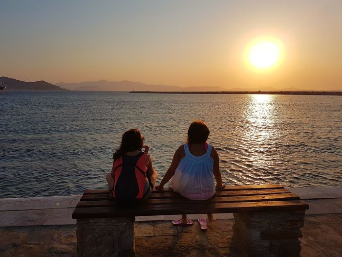 Girls Sitting On Bench By Sea Against Sky During Sunset