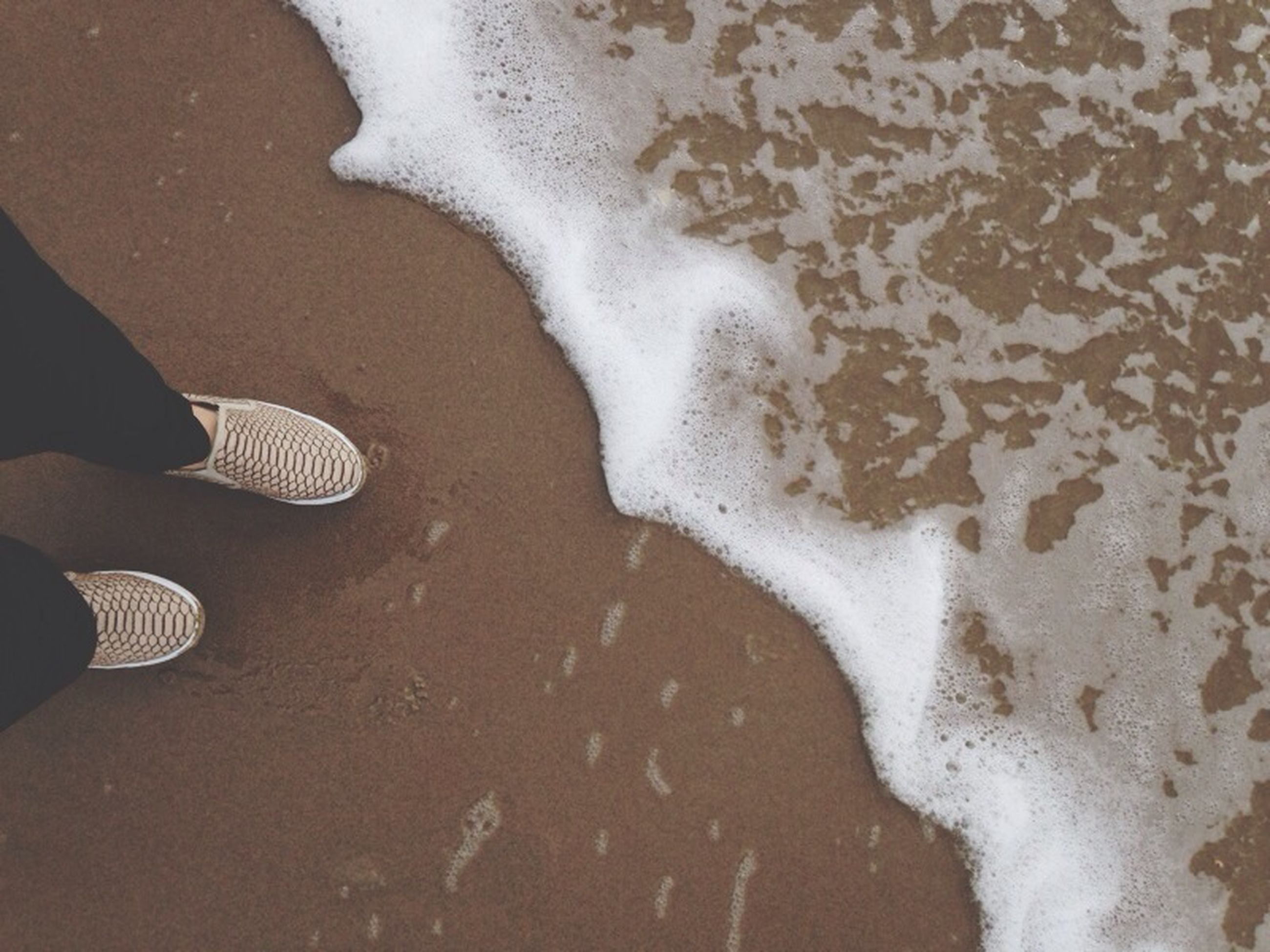 low section, person, high angle view, human foot, personal perspective, lifestyles, shoe, leisure activity, sand, standing, unrecognizable person, beach, men, footwear, part of, outdoors, day