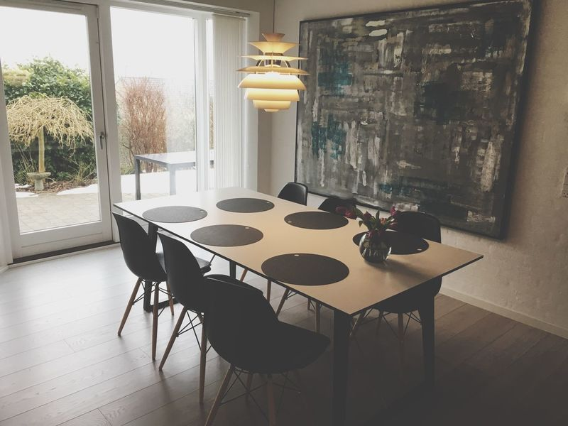 Dinner table and a large painting on the wall Living Lifestyle Table Indoors  Home Interior Window No People Chair Day Architecture