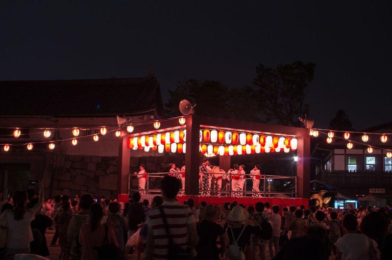 People at illuminated market against sky at night