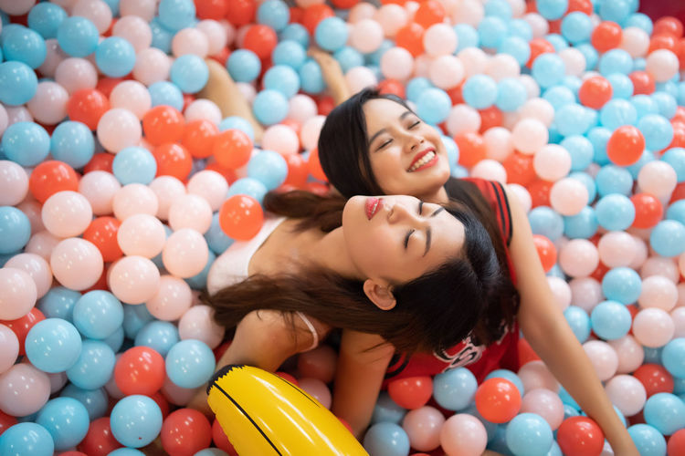 beautiful asian teenage playing at ball pool and on smartphone Happiness Smiling Women Young Adult Leisure Activity Lying Down Young Women Emotion Casual Clothing Indoors  People Multi Colored Large Group Of Objects Real People Enjoyment Lifestyles Two People High Angle View Fun Positive Emotion Hairstyle Beautiful Woman