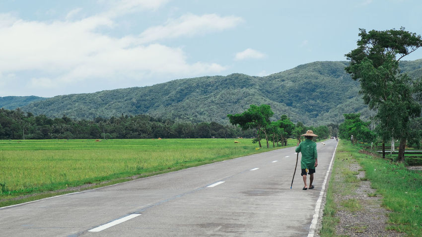 An old man walks along the roadside in Bicol province in the Philippines. Farmer Full Length Grass Leading Lines Lonely Men Mountain Old Man Philippines Rear View Road Roadside Travel Walking Walking Around Walking Away Wandering