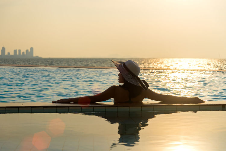 Man sitting in swimming pool against sea during sunset
